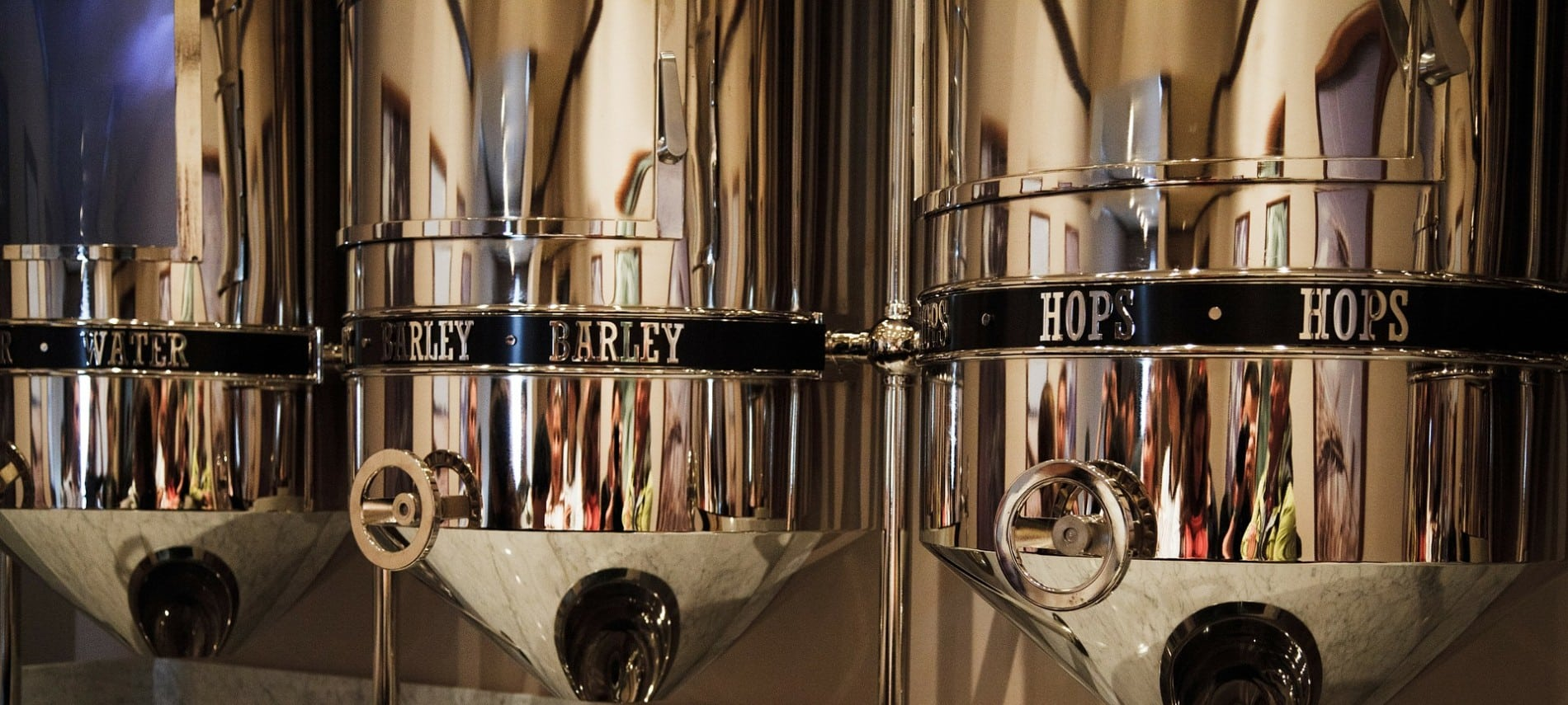 Three tall and shiny silver containers in a brewery labeled water, barley, and hops