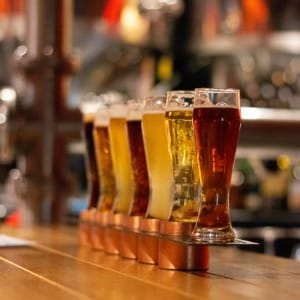 A row of seven tall clear glasses filled with different colors of beer