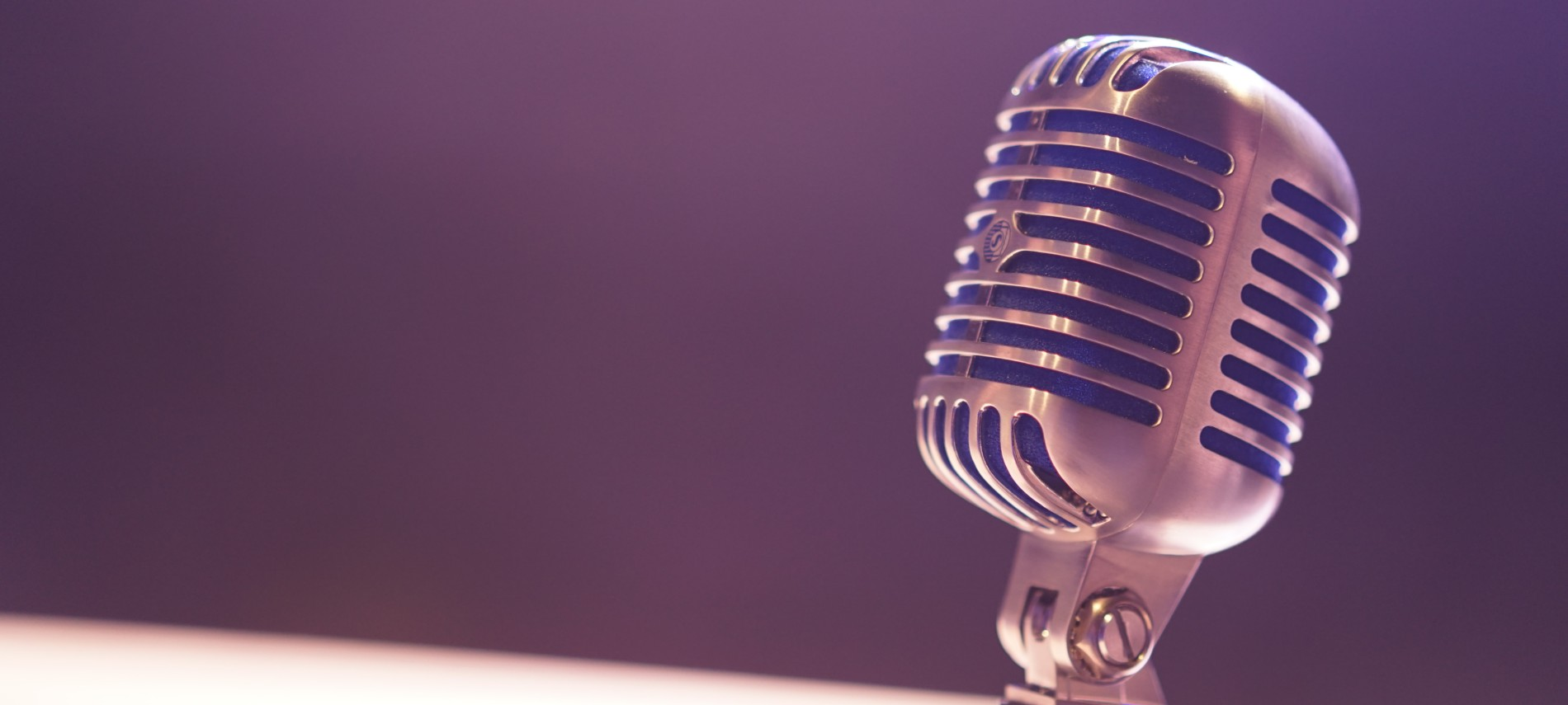 A single, silver vintage microphone against a dimly lit black background