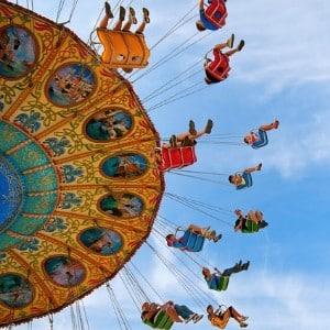 Bright yellow carnival swing ride with riders in seats swinging through the air against a blue sky
