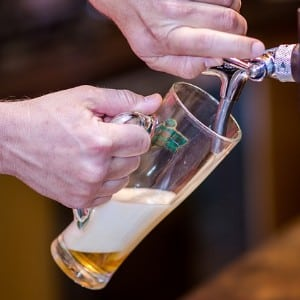 One hand holding a tall clear beer glass under a spout pouring a light yellow beer into the glass