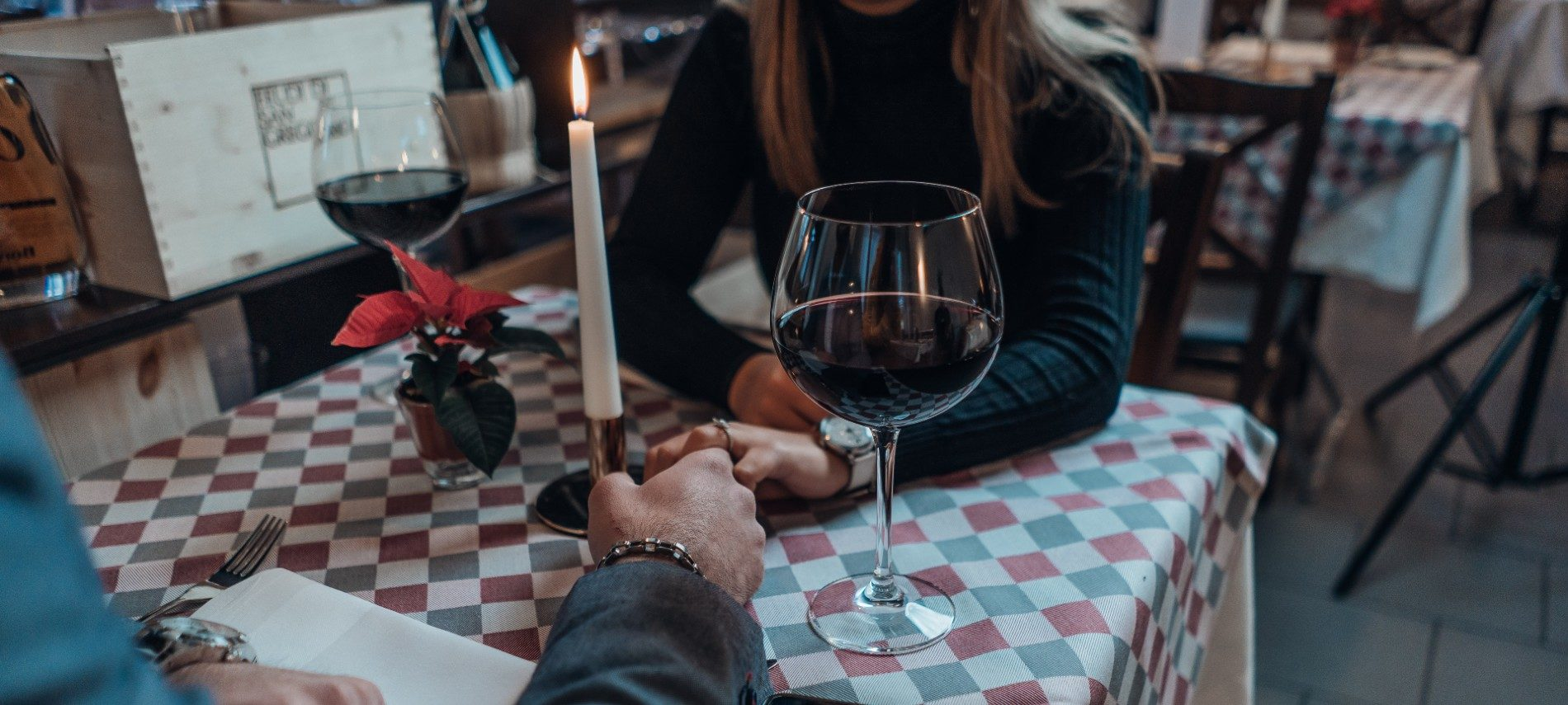 Man and woman holding hands sitting at a table for two at a restaurant