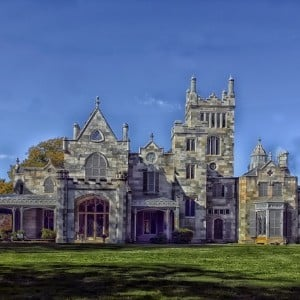 Majestic and large historic mansion built with various colors of grey stone with green lawn in front
