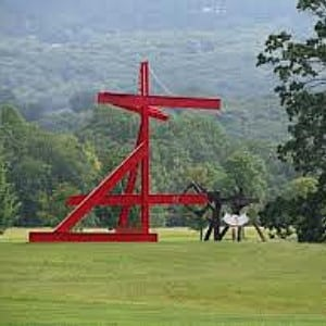 Large red metal art sculpture and small black sculpture sitting in an open field with forest in background