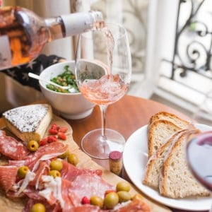 Person pouring a blush wine into one glass with a wooden tray of meats and cheese on the table