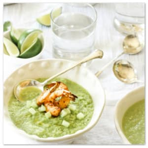 Bowl of green soup with shrimp sitting on a white tablecloth with a glass of water. Photo by lauren lester www.unsplash.com