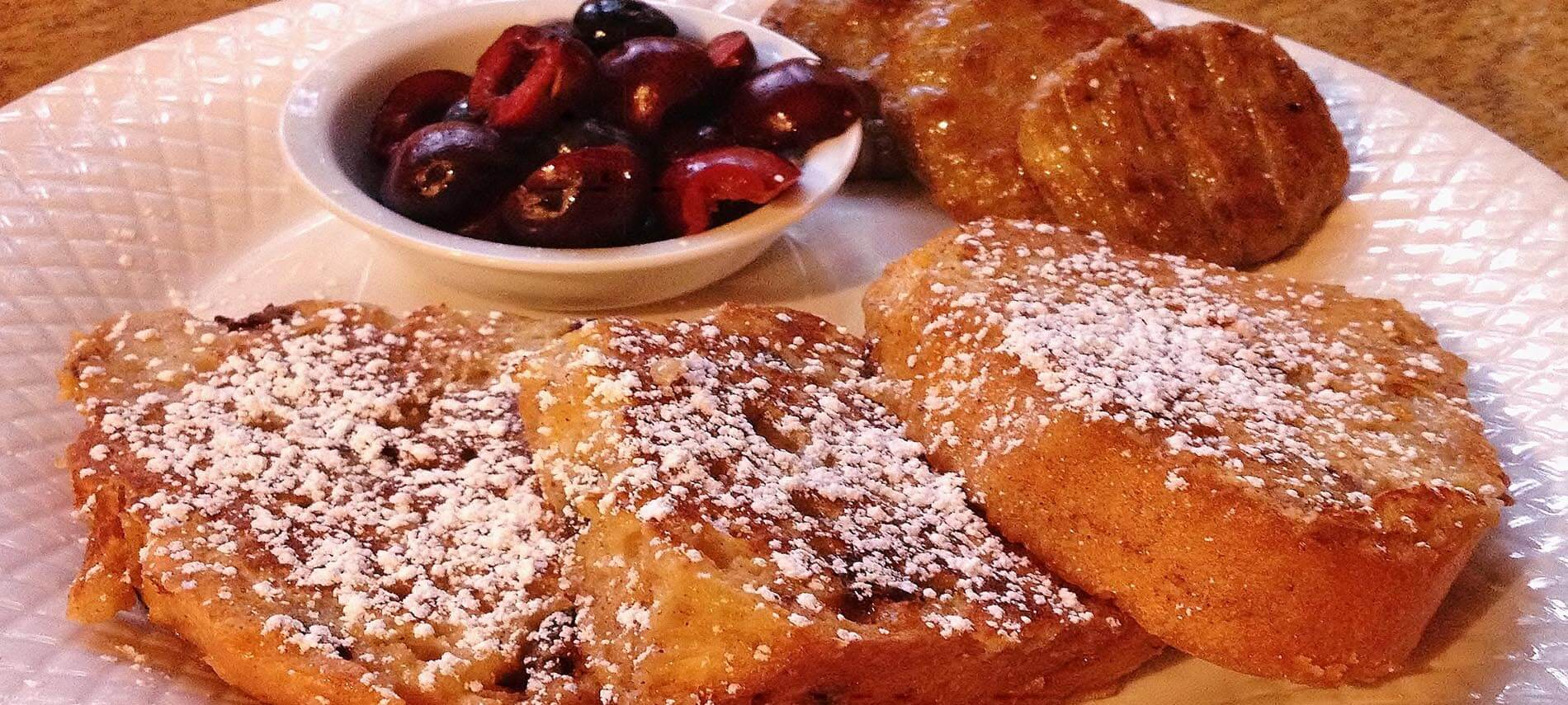 Slices of thick french toast on a white plate with a berry compote on the side,