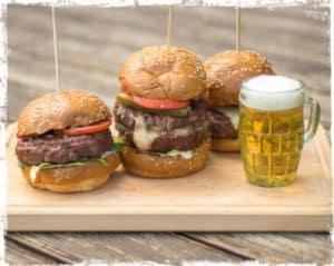Burgers next to a mug of beer