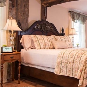 Beautiful king bed with mahogany headboard in room with wood beams and antique furniture