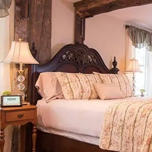 Guest room with dark wood beams, queen bed and side table with lamp