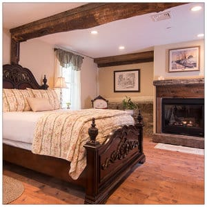 Gorgeous bedroom suite with wood beams, king bed and fireplace