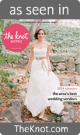 the knot magazine cover with dark brown haired bride in white strapless wedding gown with full skirt and pale pink satin sash bow at waist walking on stone path with green grass holding a bouquet