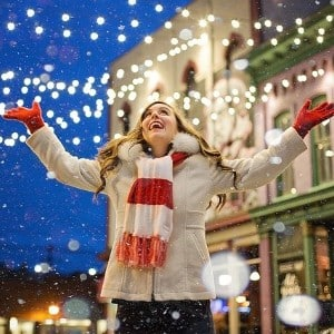 A woman in a white coat and scarf standing under white Christmas lights with snow falling