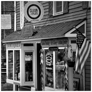 Black and white image of a quaint shop in a quiet small town with an american flag hanging