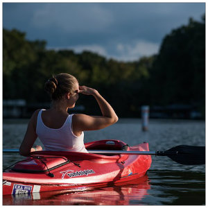 Woman in a white tank top sitting in a red kayak with the paddle across her lap