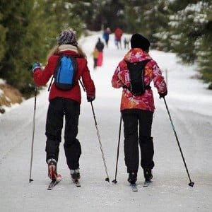 Two women cross country skiing down a snowy path surrounded by forest