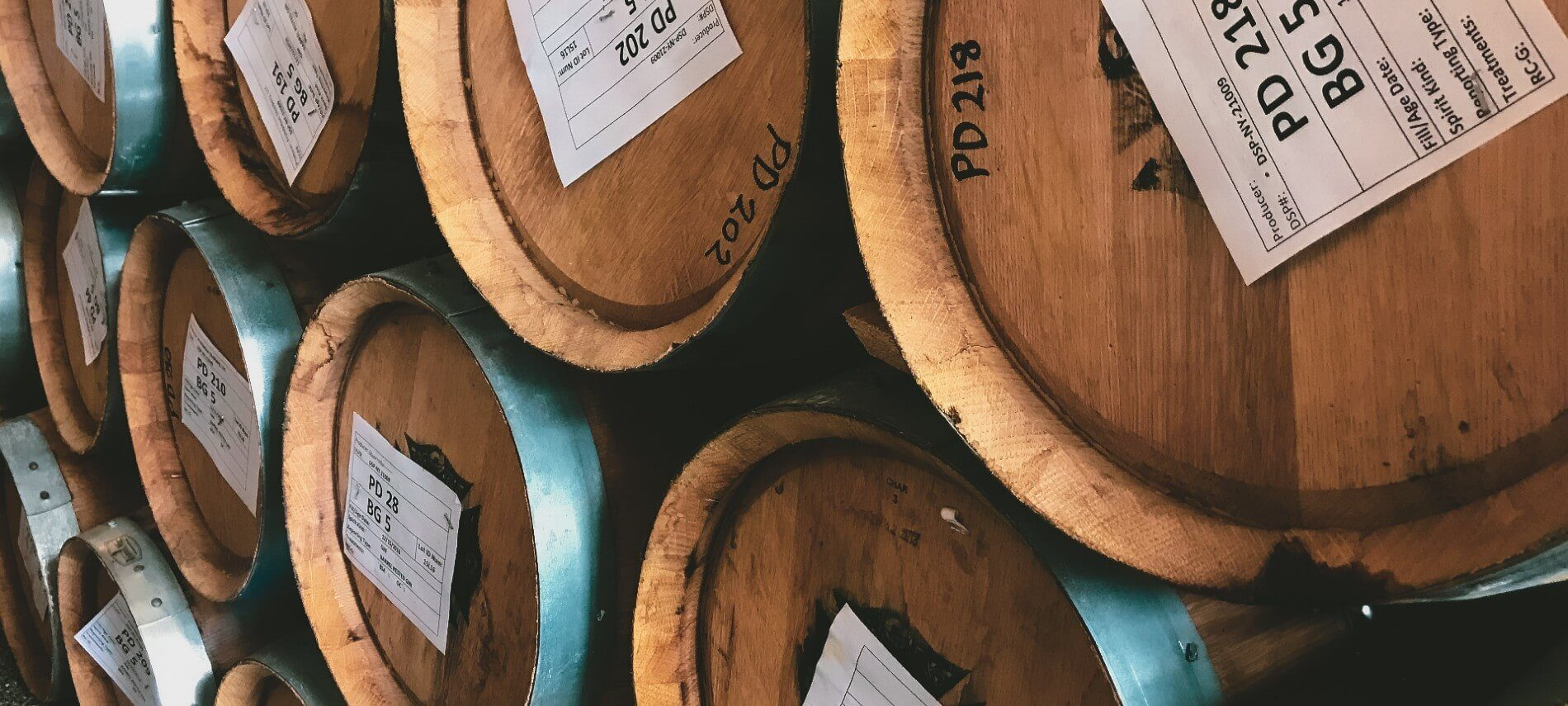 Large round barrels with silver rims and white tags in a distillery stacked on top of each other