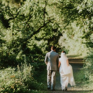 Bride in white and groom in grey tux walking a path in a green wooded forest