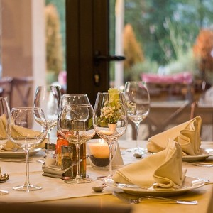 White table at a fine dining restaurant set with tall wine glasses and plates with white napkins
