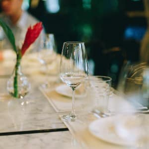 Table at a fine dining restaurant with white linens and dishes and glass stemware