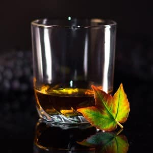 Clear glass with a little bit of rum on a black surface with a green and orang leaf