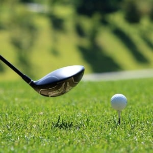 Single silver golf club hovering over a white golf ball on a tee