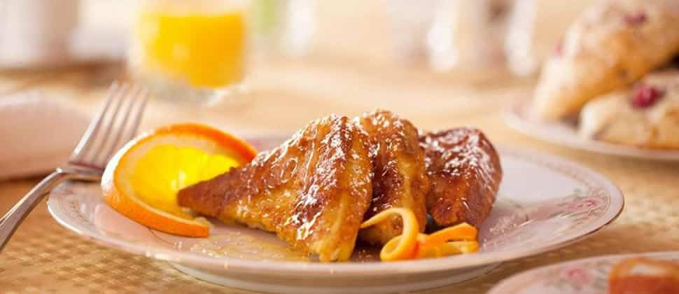 Three slices of french toast drizzled with syrup, next to bright slices of oranges.