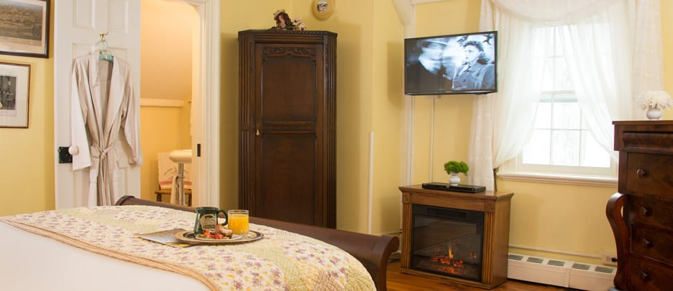 Neatly made queen bed in front of a fireplace and flat screen tv, with a tray of breakfast and orange juice.