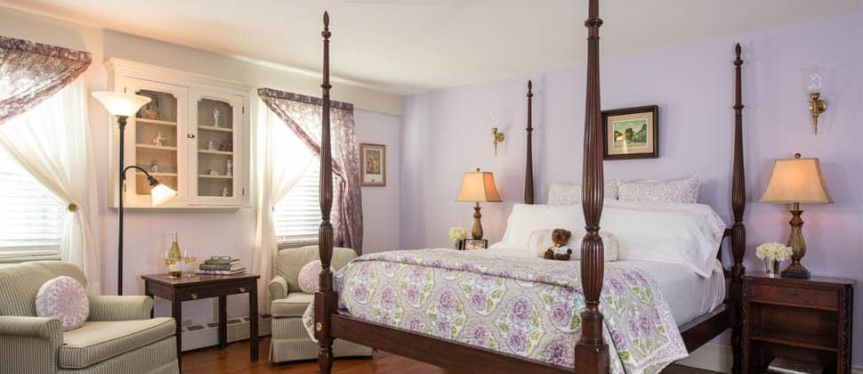Brightly lit room with lilac drapes over large windows, a comfortable linen chair and a four poster bed.