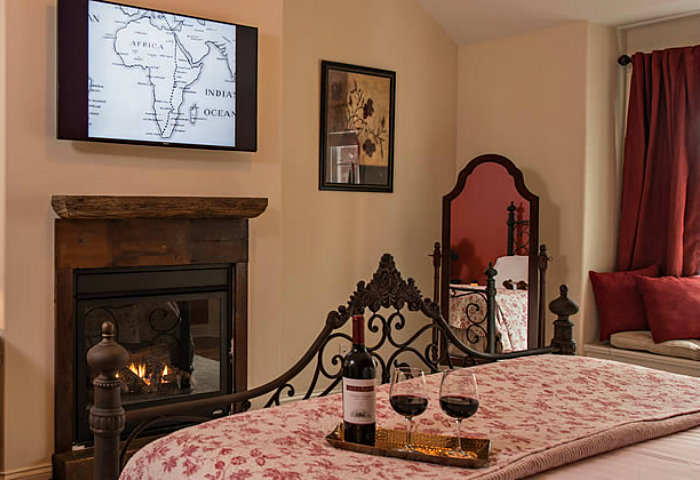 Floral quilt across a queen bed in a room with a fireplace, flat screen tv and comfortable sitting area.