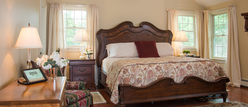 Large victorian bed in a room with vaulted ceilings and a ornate area rug.