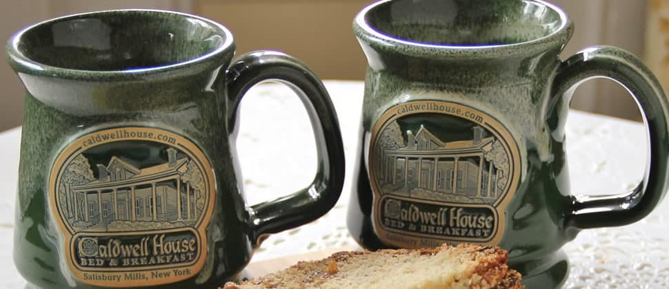 Two customized Caldwell House mugs made of green ceramic with beige lettering.