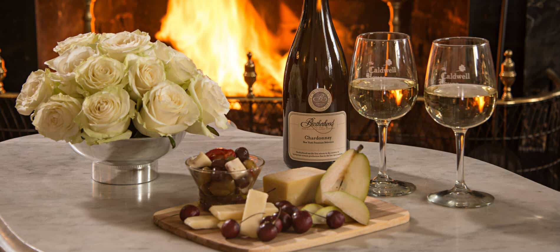 A white marble table displays fruit and cheese on tray, a bottle of Chardonnay and wine glasses; fireplace in background
