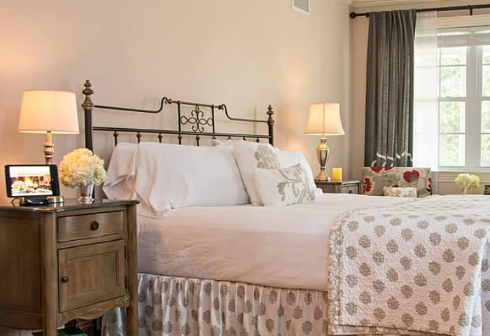 Crisp white linens on a queen bed with rought iron headboard and footboard