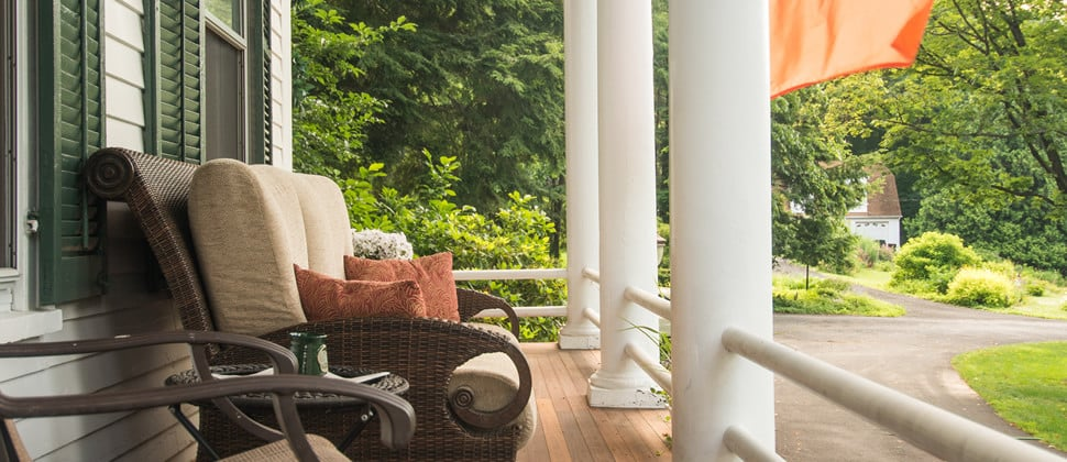 Front porch seating area with rattan furniture and plush cushions.