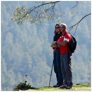 Couple hiking, standing at edge of a ridge in the mountains