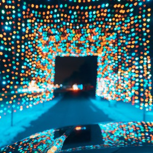 A car driving at night underneath a curtain of multi-colored Christmas lights
