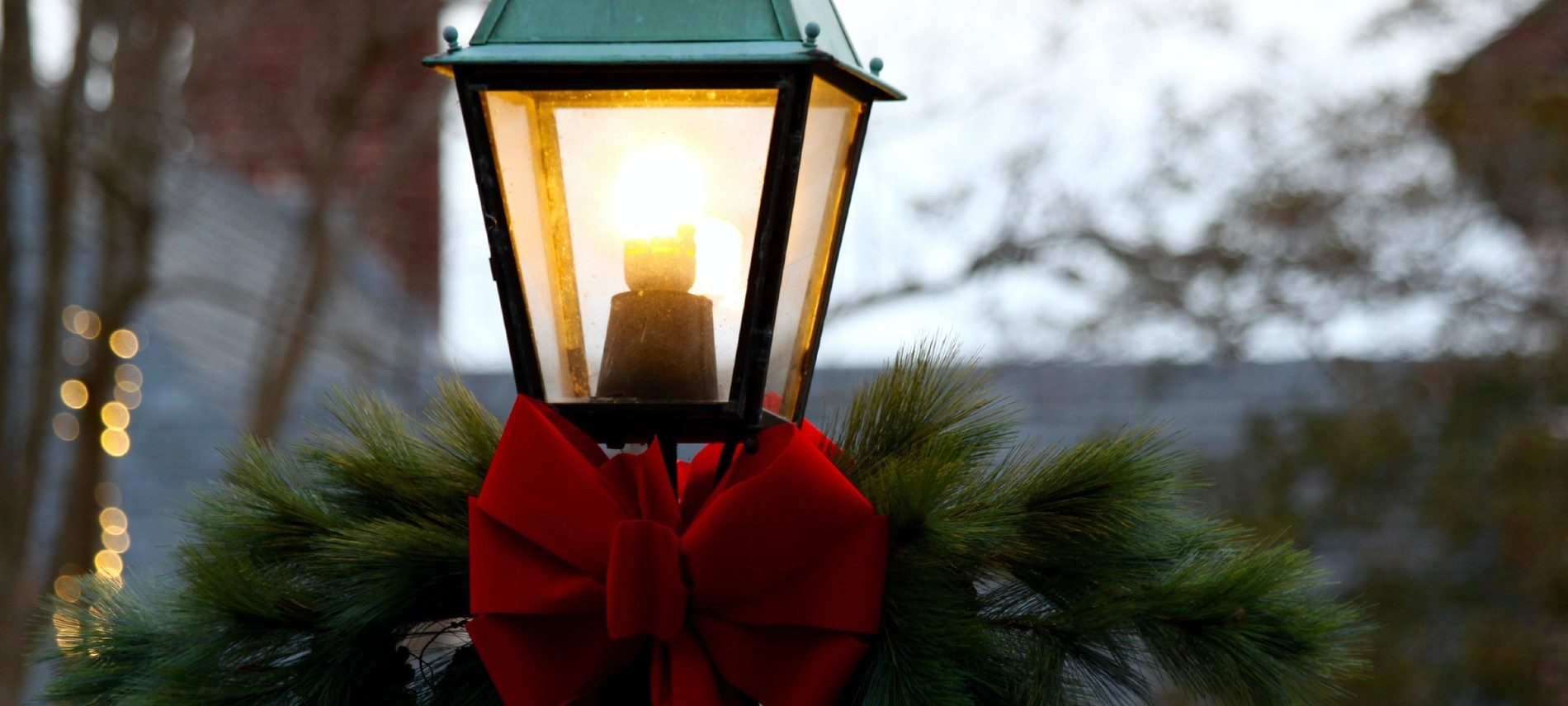 One tall black lantern lit up with greenery and a red bow at the base