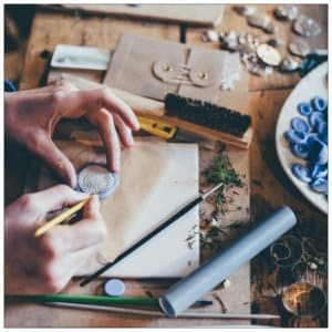 Silver jewelry maker at a table with supplies - image by annie sprat www.unsplash.com