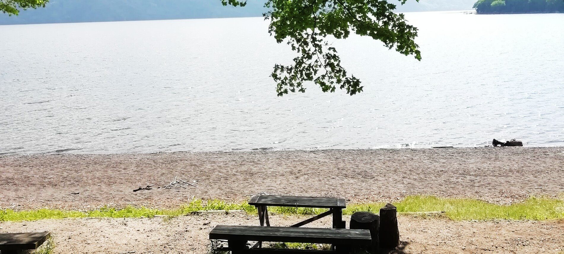 Wooden picnic bench on a deserted beach area in front of large body of water