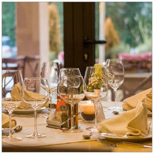 Table setting in a fine dining restaurant with white dishes and napkins, wine glasses and windows in the background