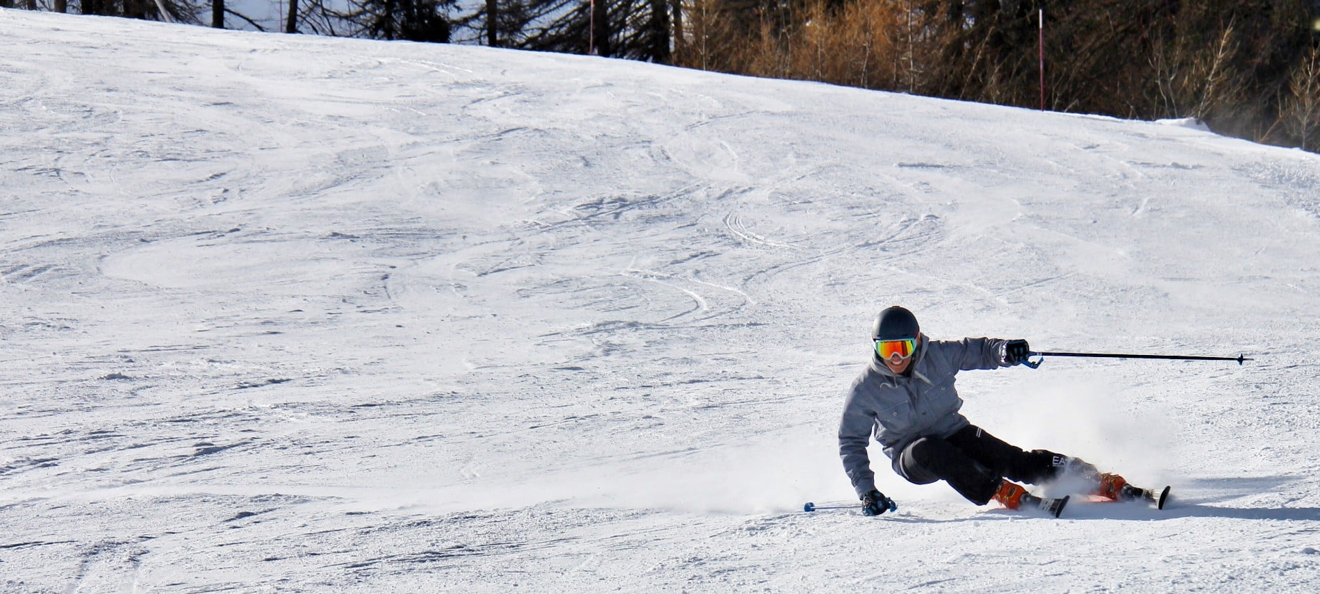 One lone skier in black pants and a blue jacket skiing down a large snow-covered hill with trees behind