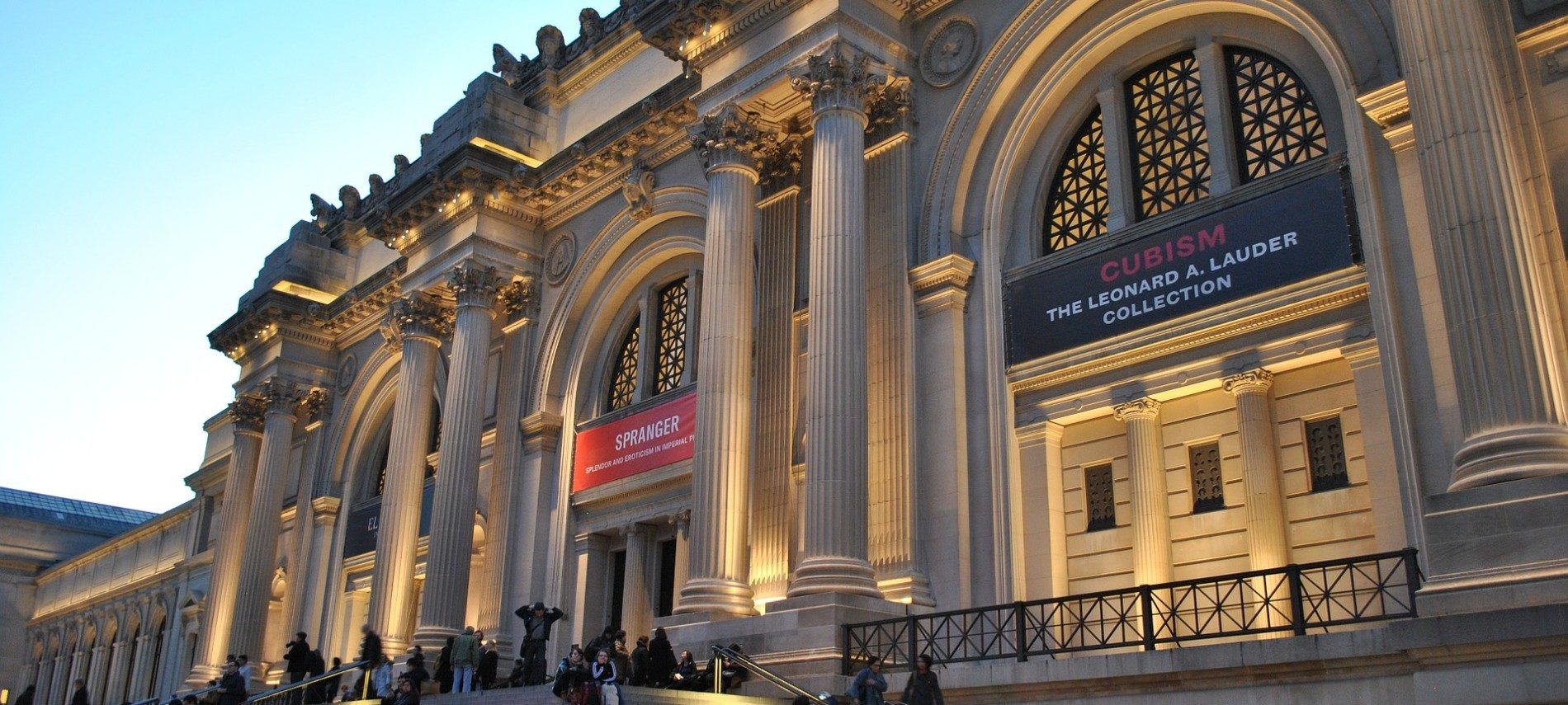 Front facade of large museum of art with tall columns, arches, and wide steps with people mingling