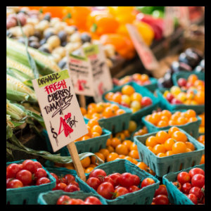 Red tomatoes, yellow corn, and other vegetables at an indoor market - photo by anne treble from www.unsplash.com