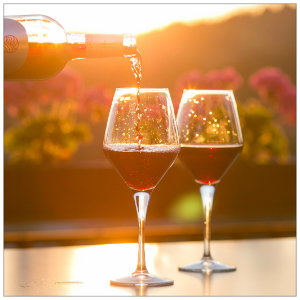 A bottle pouring red wine into two glasses sitting on a table with a winery bathed in sunset light in the background