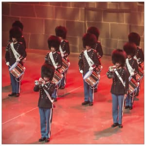 A group of military tattoo musicians in uniform on stage playing trumpets and drums