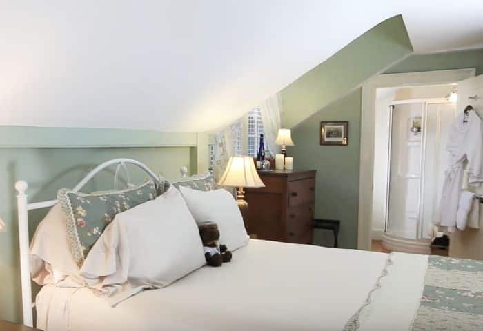 Soft green walls highlighting a white wrought iron queen bed