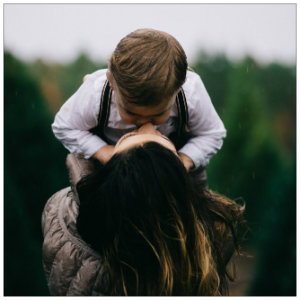 Mother holding young son up, wearing a white shirt - photo by Noah Hinton on unsplash.com