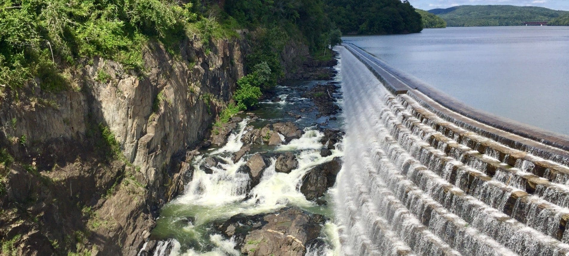 Expansive and unique retaining wall at a dam with water spilling over into a rocky gorge