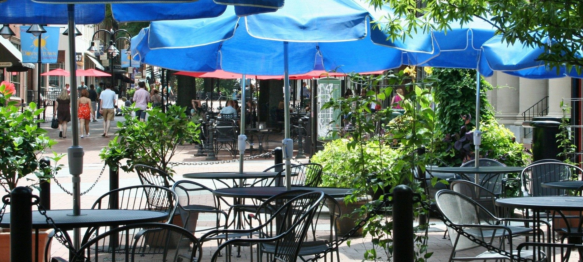 Outdoor dining area with several black tables under blue umbrellas on a street with people walking